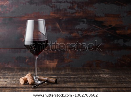 Elegant glass of red wine with corks and corkscrew on dark wooden background.