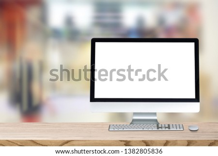 Blank screen desktop computer on plank wooden table top with blur background. Office interior with blurry background. #1382805836