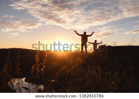 Silhouette of a free man and child enjoying freedom, feeling happy at sunset. Father and son on the edge of a cliff. Lifestyle #1382810786