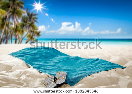Summer towel on sand. Beach background with palms and ocean. Free space for your decoration.  #1382843546