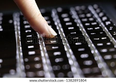 Finger on computer's keyboard. Typing on a keyboard. Laptop keyboard, notebook keyboard with black highlighted buttons.  #1382891804