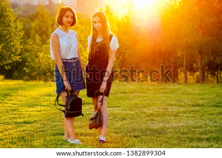 girlfriend schoolgirls stylish dress and bags backpack posing in forest the lights of a sun at sunset #1382899304