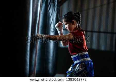 Little girl Thai boxing training is a self defense course, Muay Thai. Royalty-Free Stock Photo #1383062975
