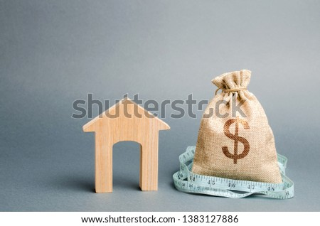 Bag with money and tape measure with a wooden house. The concept of a limited real estate budget. Low subsidies. Lack of investment in construction. Market crisis. Reduced demand for home buying #1383127886