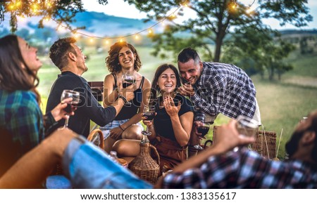 Young friends having fun at vineyard after sunset - Happy people millennial camping at open air pic nic under bulb lights - Youth friendship concept with guys and girls drinking wine at barbeque party