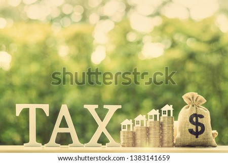House or building or land value / property tax, local development tax concept : Word tax, home model on rows of rising coins, US dollar bags on a table, depicts ad valorem tax on value of a property #1383141659