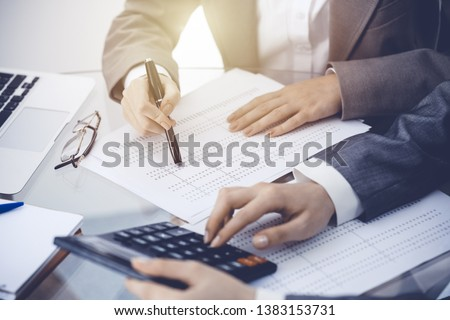 Two female accountants counting on calculator income for tax form completion hands close-up. Business and audit concept #1383153731