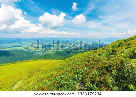 wonderful mountain landscape in summer.  green grassy hills and slopes. path downhill through the meadow. settlement and rural area in the distant valley. sunny weather with fluffy clouds on the sky #1383176234