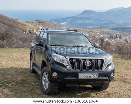 Alushta, Republic of Crimea - March 23, 2019: Black off-road car Toyota Land Cruiser Prado parked in nature #1383181064