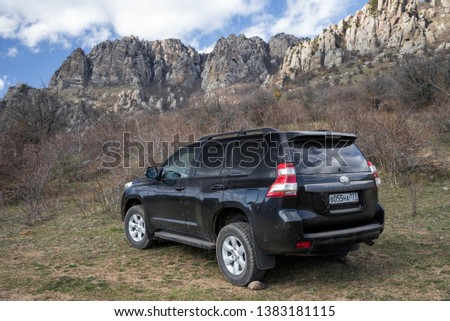 Alushta, Republic of Crimea - March 23, 2019: Black off-road car Toyota Land Cruiser Prado parked in nature #1383181115