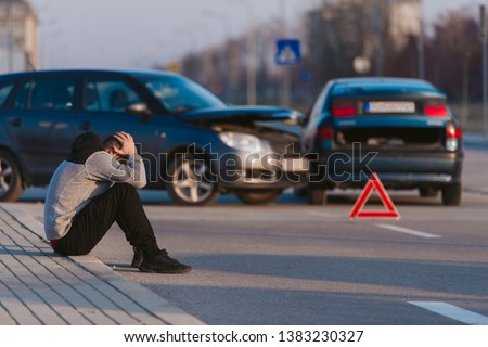 A man is looking desperate after two cars crashing on the road by his fault Royalty-Free Stock Photo #1383230327