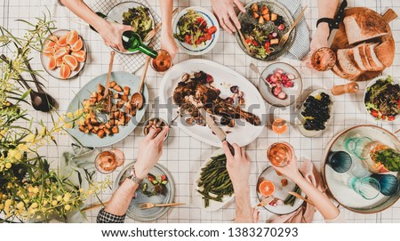 Family or friends gathering dinner. Flat-lay of hands of people eating roasted lamb shoulder, salads, vegetables, drinking rose wine over white checkered tablecloth, top view. Celebration party dinner #1383270293