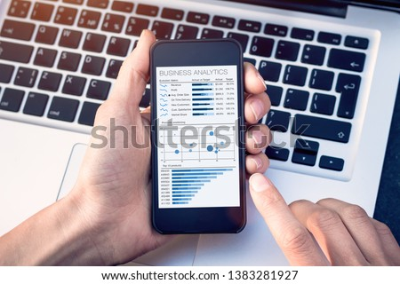 Business analytics dashboard on smartphone screen, analyst analyzing sales and operations data key performance indicators (KPI) charts and metrics #1383281927