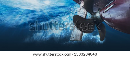 Propeller and rudder of big ship underway from underwater. Close up image detail of ship. Transportation industry. Freight transportation. Ship repair, underwater survey and shipping business concept Royalty-Free Stock Photo #1383284048