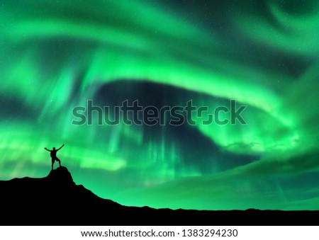 Aurora borealis and silhouette of a man with raised up arms on the mountain peak. Lofoten islands, Norway. Aurora and happy man. Sky with stars and polar lights. Night landscape with aurora and people #1383294230