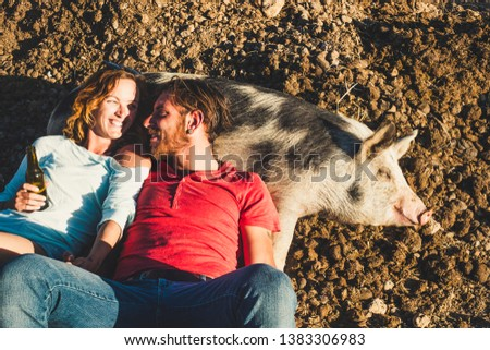 Diversity animal love pet therapy concept with young beautiful couple of young peope lay down on a nice cheerful pig sleeping on the ground in a sunny day - alternative lifestyle with nature rural Royalty-Free Stock Photo #1383306983