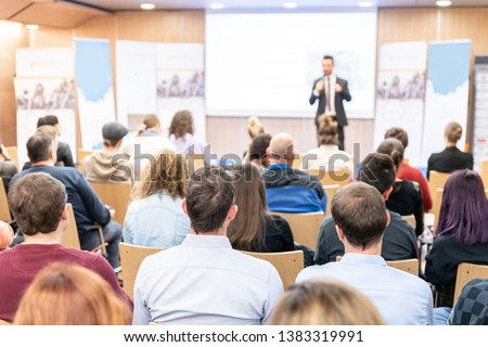 Speaker giving a talk in conference hall at business event. Audience at the conference hall. Business and Entrepreneurship concept. Focus on unrecognizable people in audience. #1383319991