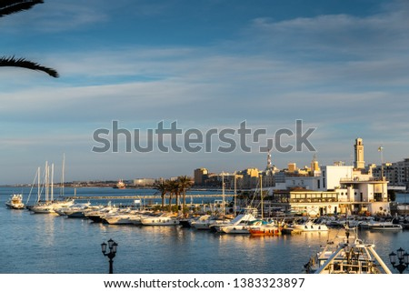 Bari, Italy - March 10, 2019: Sunset view of the touristic seafront and port of Bari, with its ferris wheel in the background. #1383323897