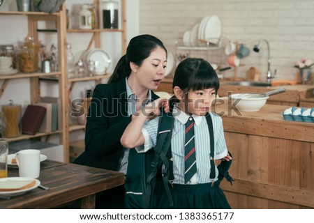 young mother worker in business suit help daughter get ready for school. Mom support child to wear backpack bag in wooden kitchen talking nag to little girl after breakfast time leaving home to study #1383365177