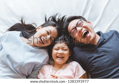 Happy Asian family laying on bed in bedroom with happy and smile, top view #1383393977