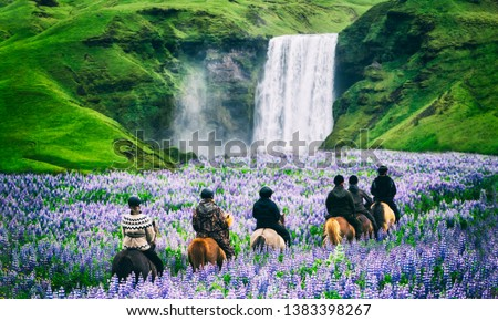 Tourists ride horses at the majestic Skogafoss Waterfall in countryside of Iceland in summer. Skogafoss waterfall is top famous natural landmark and travel destination place of Iceland and Europe. #1383398267