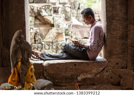 Siem Reap, Cambodia, September 8th 2018 : Local guide taking a break while using his phone at Bayon temple in Siem Reap, Cambodia #1383399212