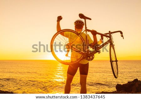 Success, achievement and winning concept with cyclist man road biking. Happy male professional athlete cycling raising arms lifting bike by sea during sunset cheering and celebrating at summit top. #1383437645