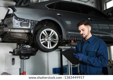 Technician checking car on hydraulic lift at automobile repair shop #1383449957