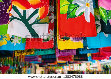 Sarong skirts shop at city market of Papeete, Tahiti, French Polynesia. Colorful clothing pareo wrap hanging for sale as handmade tourism souvenir. #1383478088