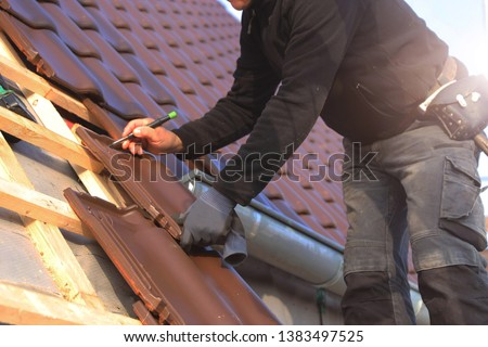 Roofing contractor tiling a roof #1383497525