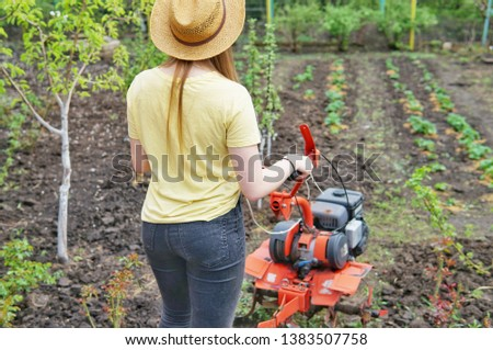 A young girl farmer in a yellow T-shirt stands in front of a small garden with a motor-cultivator and prepares to plow a vegetable garden. #1383507758