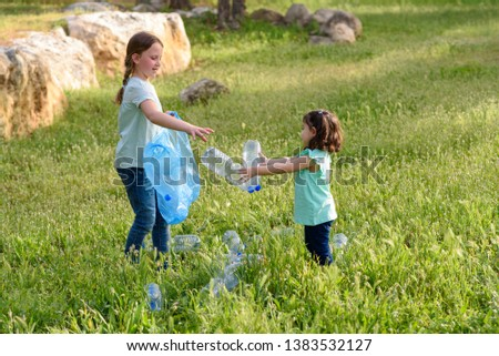 Cute little girls cleaning up plastic litter on grass. Children Volunteers cleaning up litter and putting plastic bottle into recycling bag. #1383532127