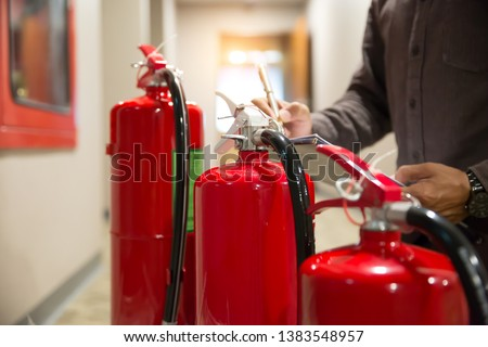 Engineers are checking fire extinguishers. #1383548957