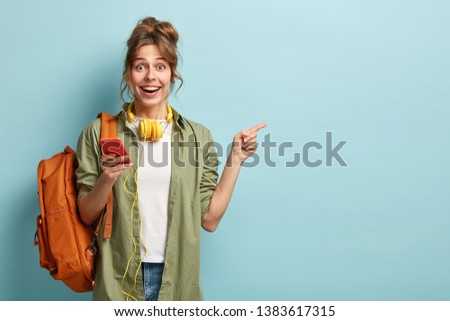Studio shot of happy teenage girl holds mobile phone, checks email, gets new notification, uses modern headphones, points at copy space for brand name or label, wears loose khaki shirt, carries bag #1383617315