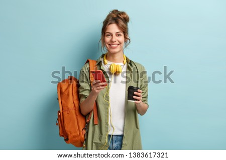 Studio shot of glad female student has coffee break after lectures, listens audio book in headphones, enjoys record from website, uses mobile phone for chatting online, has rucksack on back. #1383617321