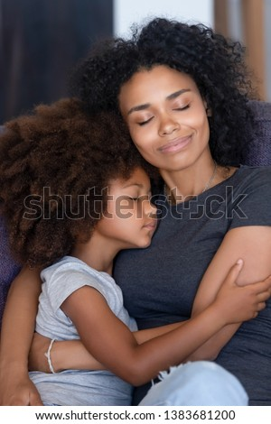 Young African American mommy relax on couch hugging little cute daughter falling asleep together, loving black mom cuddle with small kid, caressing folding to breast, have close tender moment #1383681200