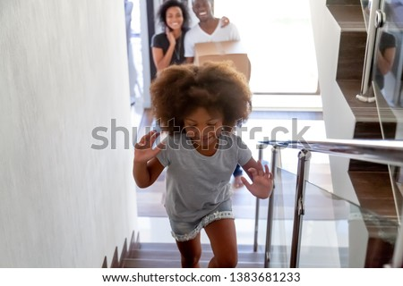 Happy funny African American kid run upstairs new house on moving day with parents, excited black girl have fun exploring own home when relocating with mom and dad. Relocation, mortgage concept #1383681233