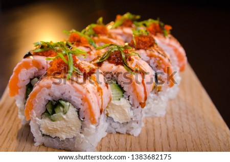 Beautiful sushi rolls with tuna on a wooden plank. Japanese sushi with fish in the Ukrainian seafood restaurant. Menu rolls on a black background #1383682175