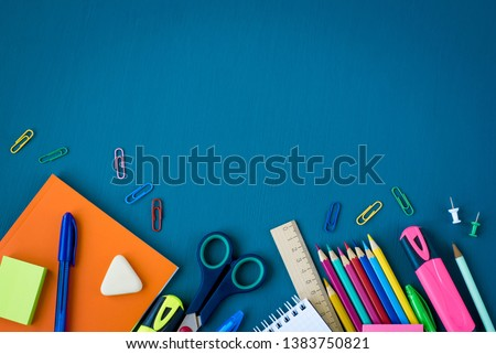 School supplies on blue background. Top view. Copy space. Royalty-Free Stock Photo #1383750821