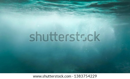 Abstract photo of lots of bubbles floating in clear turqouise sesa water
