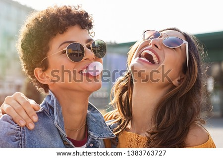 Young latin woman laughing while friend inflating bubble gum. Closeup face of multiethnic friends enjoying outdoor street. Brazilian girl laughing and blowing chewing gum with friend embracing her. Royalty-Free Stock Photo #1383763727