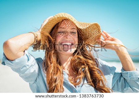 Closeup face of mature woman wearing straw hat enjoying the sun at beach. Happy woman smiling during summer vacation at sea.Beautiful lady relaxing at beach while holding large brim for the wind. #1383763730