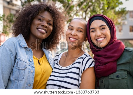 Group of three happy multiethnic friends looking at camera. Portrait of young women of different cultures enjoying vacation together. Smiling islamic girl with two african american friends outdoor. #1383763733