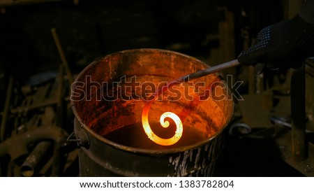 Professional blacksmith working with metal - quenching hot iron part of forged gate in water at forge, workshop. Handmade, craftsmanship and blacksmithing concept #1383782804