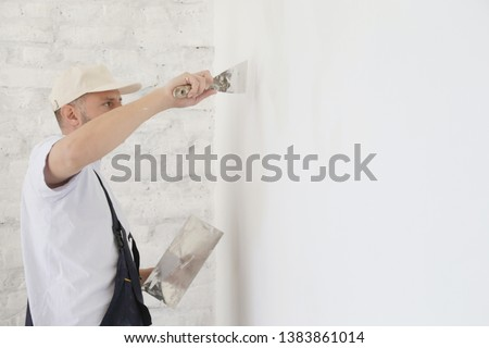 Man plastering wall with putty-knife, close up image. Fixing wall surface and preparation for painting.  #1383861014