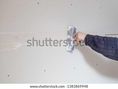 Worker aligns the walls with plaster. Repair in the house. #1383869948