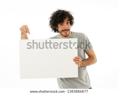 Funny and good looking millennial man showing and pointing at blank board with copy space for text. Friendly and excited young stylish man holding blank poster for advertisement. In marketing concept.
