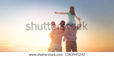 happy family at sunset. father, mother and two children daughters having fun and playing in nature. the child sits on the shoulders of his father. #1383945242