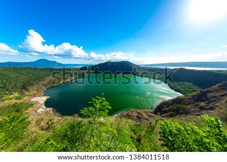 View of cones of Taal Volcano and the wind ruffled emerald green water in the Lake Taal on a sunny day in Tagaytay, Philippines. #1384011518