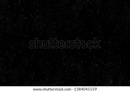 Abstract real dust floating over black background Royalty-Free Stock Photo #1384045559